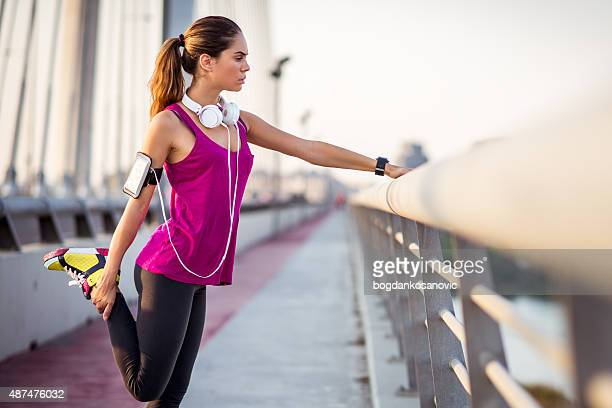 Young woman stretching leg after running