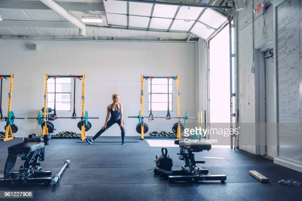 young woman stretching legs against wall in health club - warming up stock pictures, royalty-free photos & images
