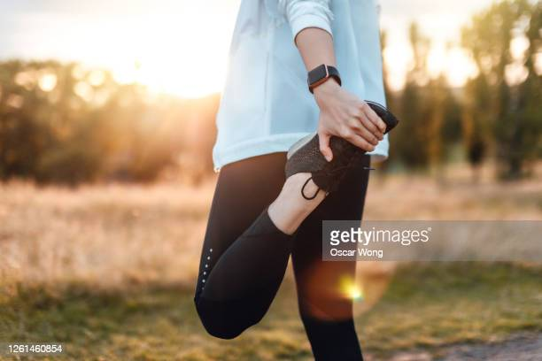 young woman stretching legs in the park after exercise - sports training stock pictures, royalty-free photos & images