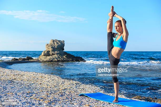 Young woman stretching legs on beach