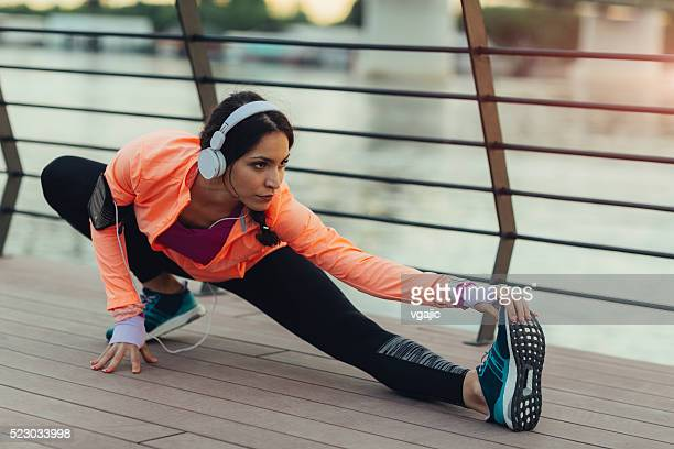 Young Woman Stretching Near River.