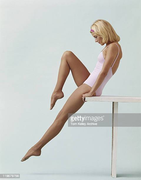 young woman stretching on balance beam - leotard stock photos and pictures