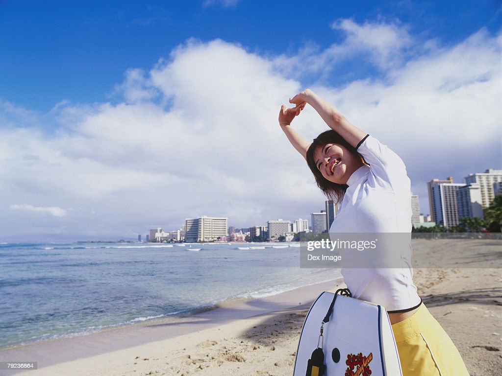 Young woman stretching on beach, paddleboard leaning on her body : Stock Photo