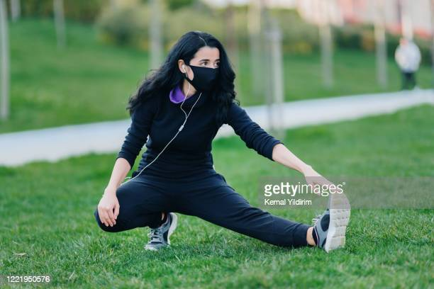 young woman stretching on grass in public park - warm up exercise stock pictures, royalty-free photos & images
