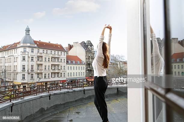 young woman stretching on roof terrace - 日曜日 ストックフォトと画像