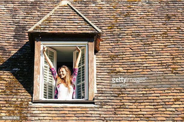 Young woman stretching on rooftop window