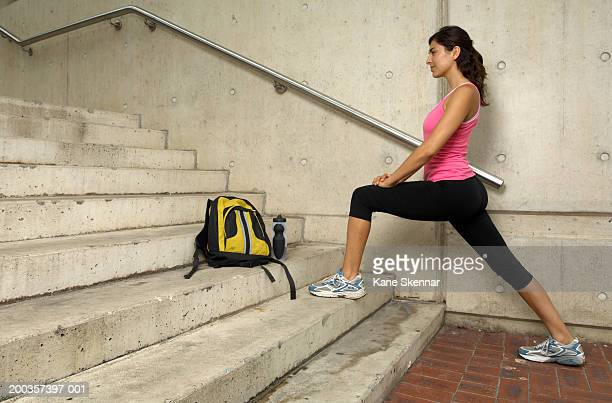 Young woman stretching on steps, side view
