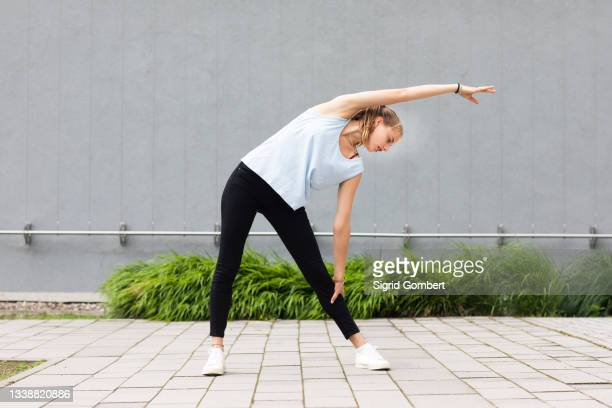 young woman stretching outdoors - sigrid gombert stock pictures, royalty-free photos & images