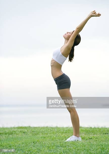 Young woman stretching, side view, outdoors