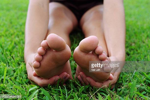 Young woman stretching, touching bottom of feet, close-up