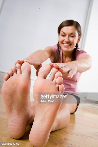 young woman stretching, touching toes (focus on soles of feet) - female feet soles stock photos and pictures