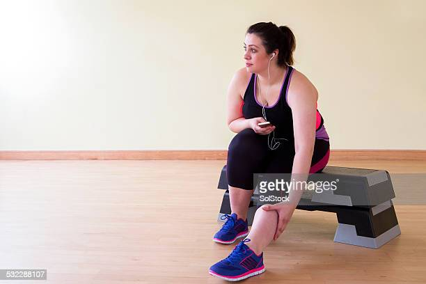 young woman stretching wearing earphones - chubby legs stock photos and pictures