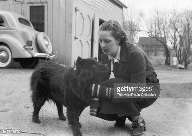 Young woman stroking a Chow Chow dog with motor vehicle in the background, US circa 1940.