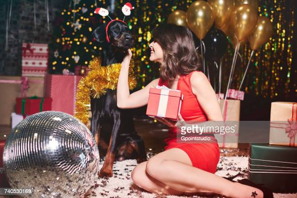 Young woman stroking dog at party, dog wearing santa deely boppers