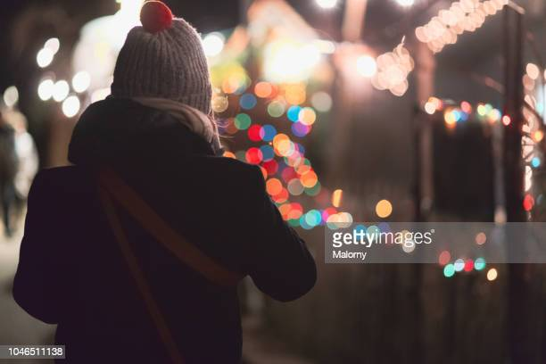 young woman strolling across a christmas market in germany. - one night stand stock-fotos und bilder