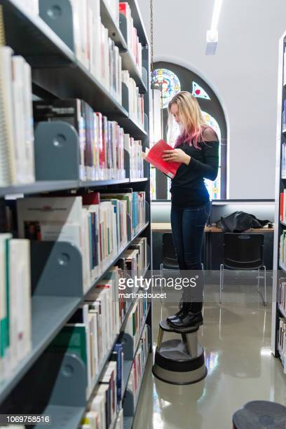 """young woman student choosing books in college library. - """"martine doucet"""" or martinedoucet stock pictures, royalty-free photos & images"""