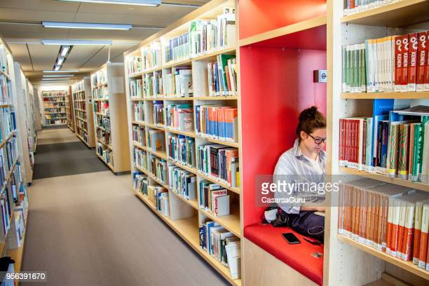 Young Woman Student Using Laptop and Mobile Phone in Library