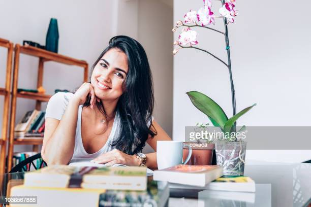 young woman studying at home looking