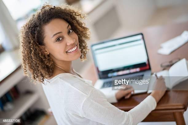 Jeune femme étudie à la maison