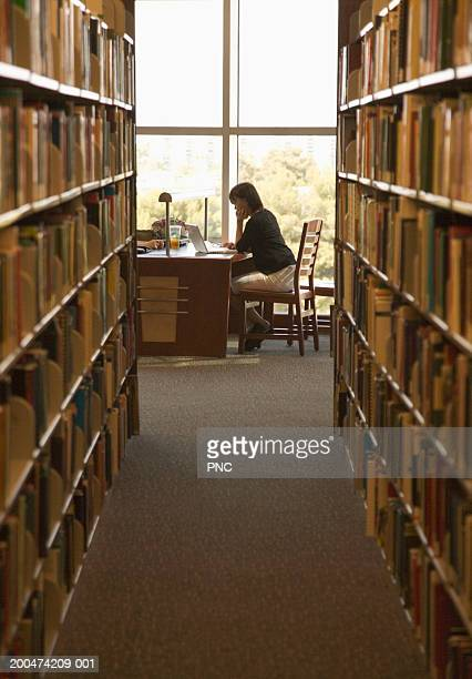 Young woman studying in library, resting chin on hand, side view