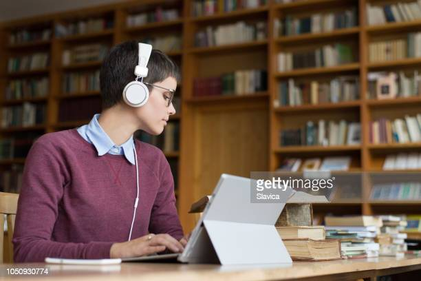 young woman studying in the library - authors foto e immagini stock