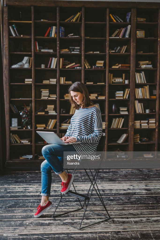 Young woman studying in the library : Stock Photo