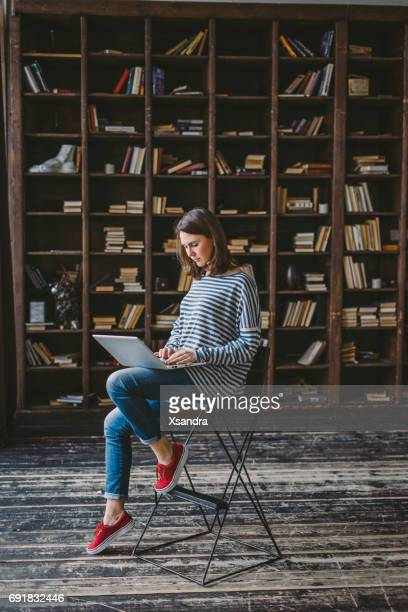 young woman studying in the library - book store stock photos and pictures
