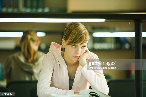 Young woman studying in university library, holding head, looking away