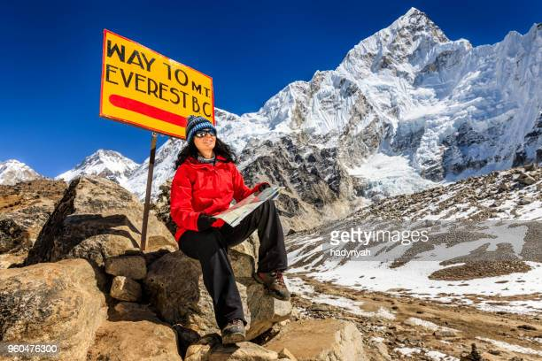 Young woman studying map next to signpost, Nepali Himalaya