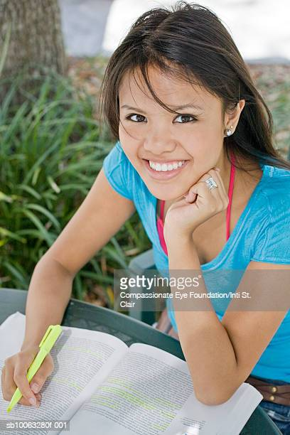 """young woman studying with textbook outdoors, smiling, portrait - """"compassionate eye"""" stock pictures, royalty-free photos & images"""