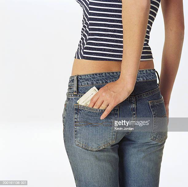 Young woman stuffing money into back pocket, mid section, rear view