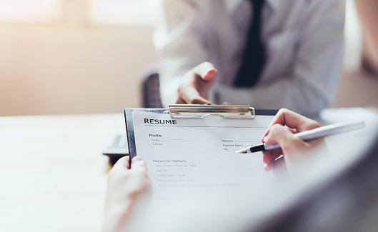 Young woman submit resume to employer to review job application. The concept presents the ability for the company to agree with the position of the job. 1010098830