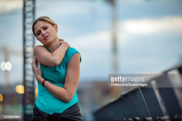young woman suffered a shoulder injury during morning exercise - injured stock pictures, royalty-free photos & images