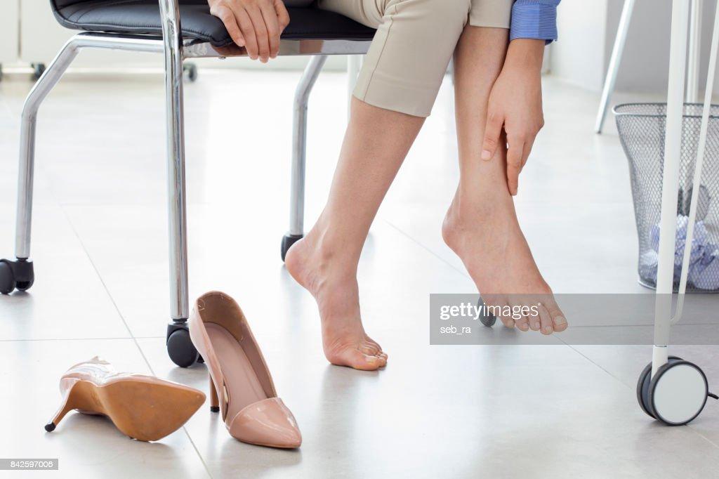 オフィスでの足の痛みから苦しんでいる若い女性 : ストックフォト