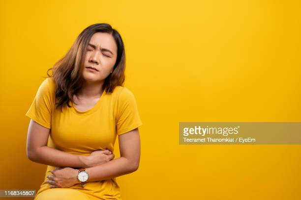 young woman suffering from stomachache sitting against yellow background - 腹痛 ストックフォトと画像