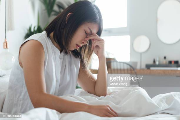 young woman suffering headache in bed - headache stock pictures, royalty-free photos & images