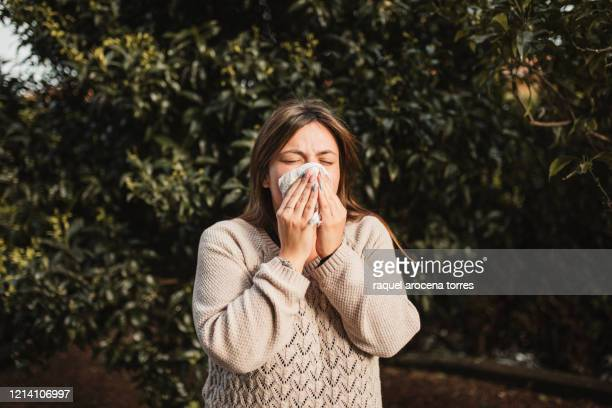 young woman suffering spring allergy and blowing nose with a tissue in the nature - mucus stock pictures, royalty-free photos & images