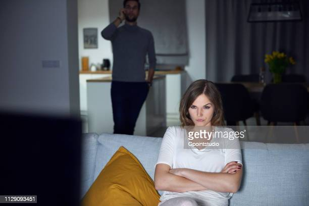 Young woman sulking on sofa in evening, while boyfriend makes smartphone call