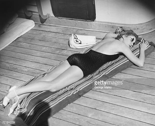 Young woman sun tanning on cruiser deck (B&W), elevated view