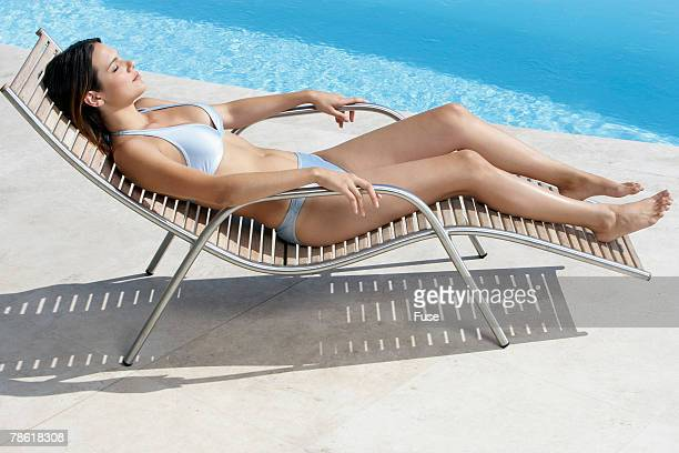 Young Woman Sunbathing by Poolside