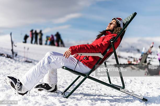 Young woman sunbathing in deck chair during winter day.