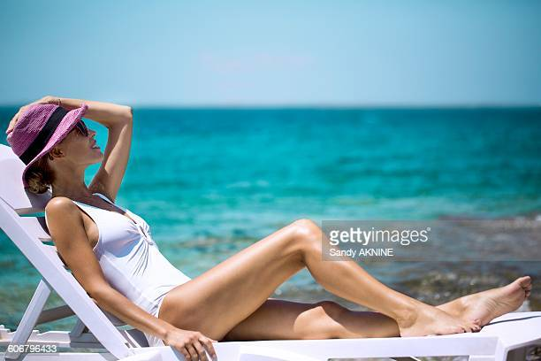 Young woman sunbathing on a deckchair