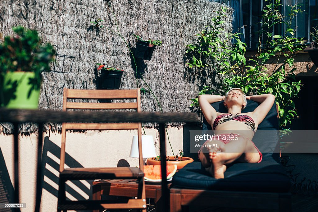 Young woman sunbathing on deck chair on her terrace : Stockfoto