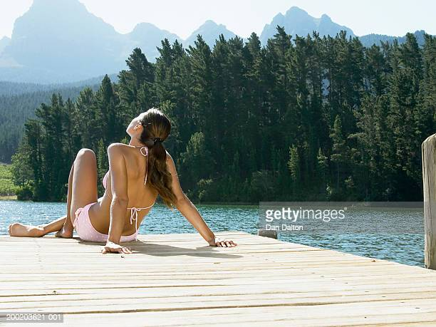 Young woman sunbathing on jetty by lake, rear view