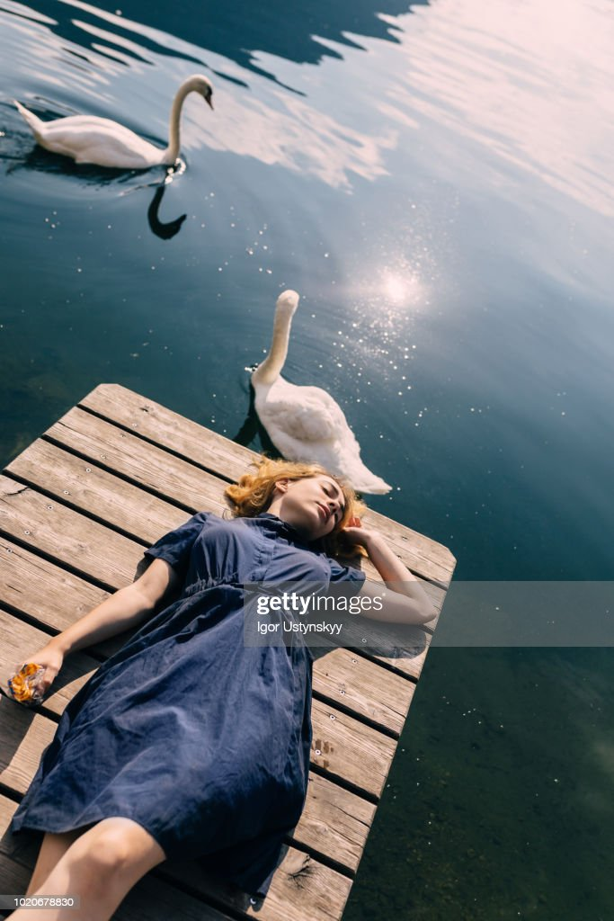 Young woman sunbathing on jetty : Stock Photo