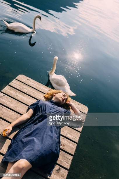 Young woman sunbathing on jetty