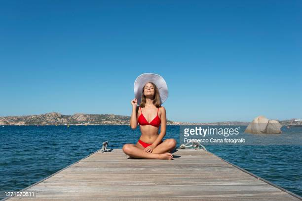 young woman sunbathing on wooden pier - sunbathing stock pictures, royalty-free photos & images