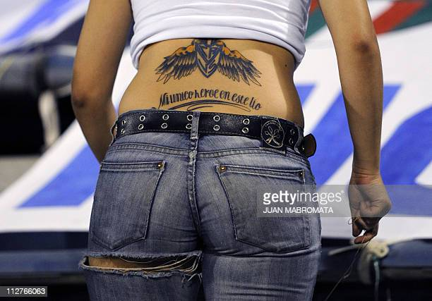 A young woman supporter of Argentina's Velez Sarsfield displays a tattoo with her team shield and a legend reading 'My only hero in this mess' during...