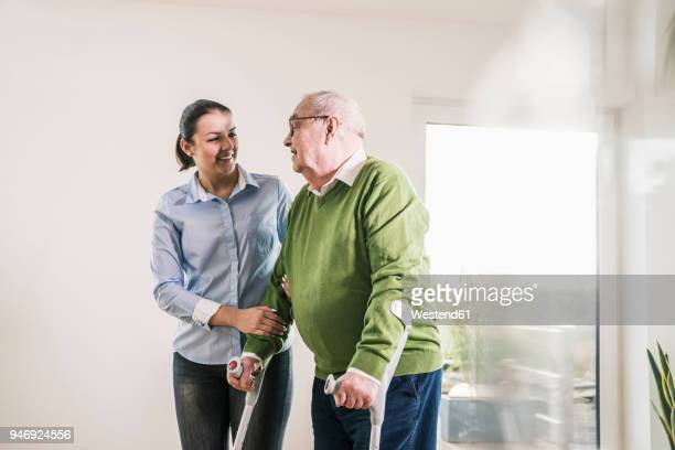 young woman supporting senior man walking on crutches - outpatient care stock pictures, royalty-free photos & images