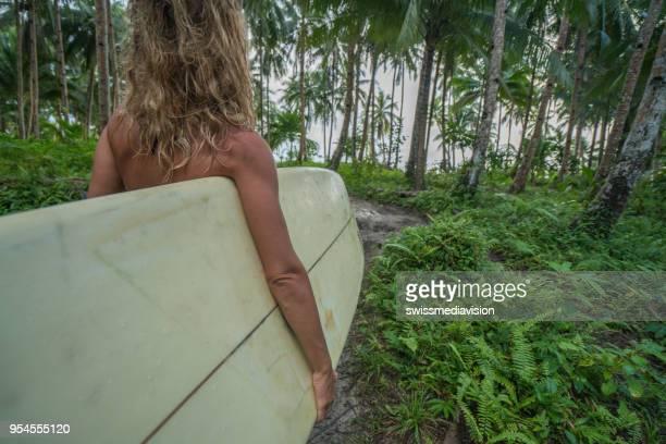 Junge Frau Surfen Mädchen halten Longboard walking am Strand, das Meer unter den Palmen auf den Philippinen-Inseln. Die Leute Reisen Urlaub-Sport-Konzept.